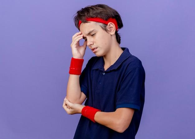 Dolorante giovane bel ragazzo sportivo che indossa la fascia e braccialetti di toccare la testa tenendo la mano sul gomito guardando verso il basso che soffrono di mal di testa isolato