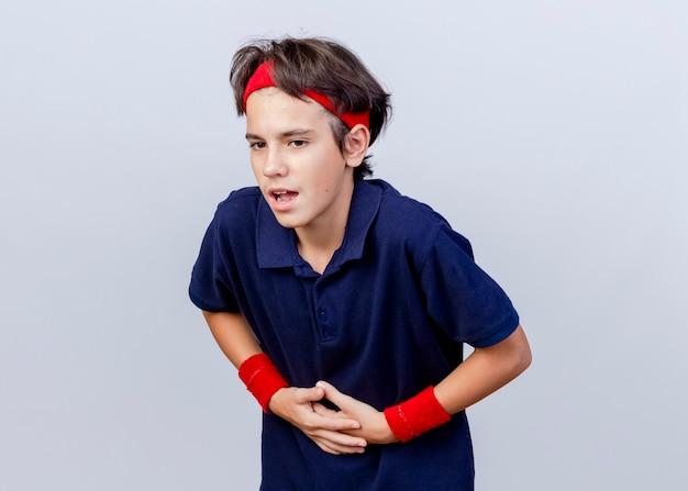 Dolorante giovane bel ragazzo sportivo che indossa la fascia e braccialetti con bretelle dentali guardando verso il basso tenendo la pancia isolato su sfondo bianco con spazio di copia