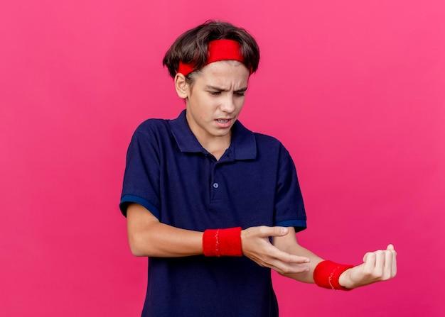 Giovane ragazzo sportivo bello dolorante che indossa la fascia e i braccialetti con le parentesi graffe dentali che osserva e che indica con la mano al suo polso isolato sulla parete rosa con lo spazio della copia