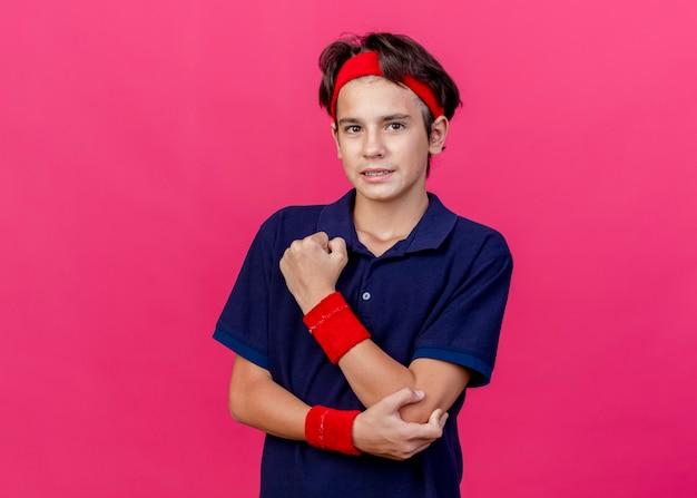 Giovane ragazzo sportivo bello dolorante che indossa la fascia e braccialetti con le parentesi graffe dentali che mettono la mano sul gomito che guarda l'obbiettivo isolato su priorità bassa cremisi con lo spazio della copia