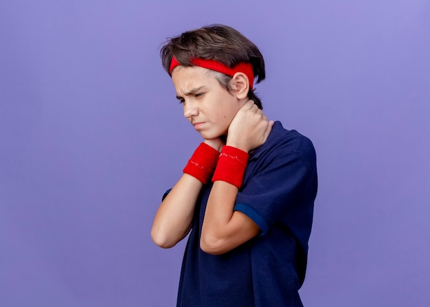 Aching young handsome sporty boy wearing headband and wristbands with dental braces standing in profile view looking down keeping hands behind neck isolated on purple wall with copy space