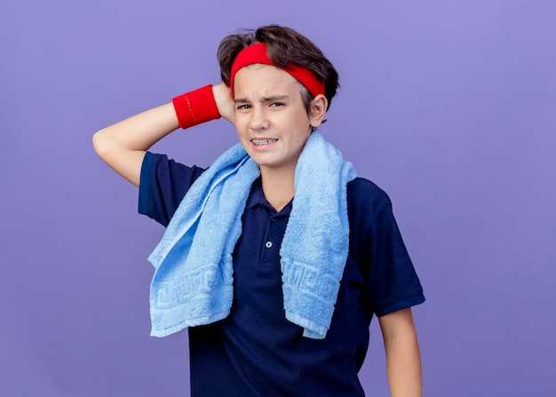 Aching young handsome sporty boy wearing headband and wristbands with dental braces and towel around neck isolated on purple wall