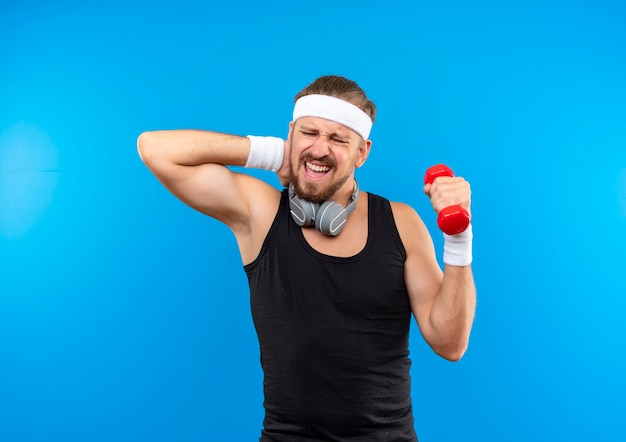 Aching young handsome sporty man wearing headband and wristbands and headphones around neck holding dumbbell and putting hand on neck isolated on blue wall