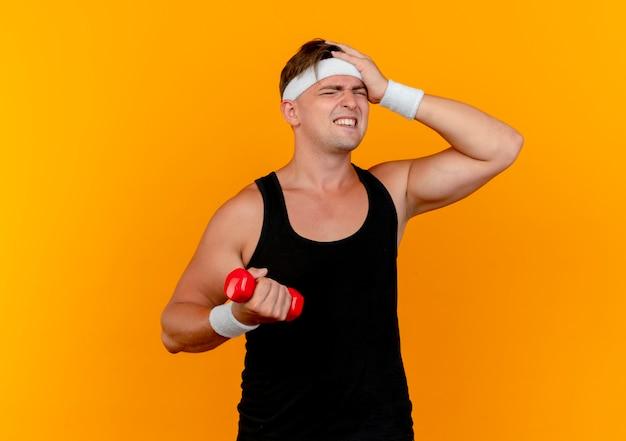 Dolorante giovane uomo sportivo bello che indossa la fascia e braccialetti tenendo il manubrio mettendo la mano sulla testa isolata sull'arancio con lo spazio della copia