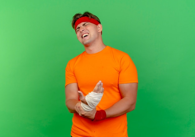 Aching young handsome sporty man wearing headband and wristbands holding his injured wrist wrapped with bandage with closed eyes isolated on green  with copy space