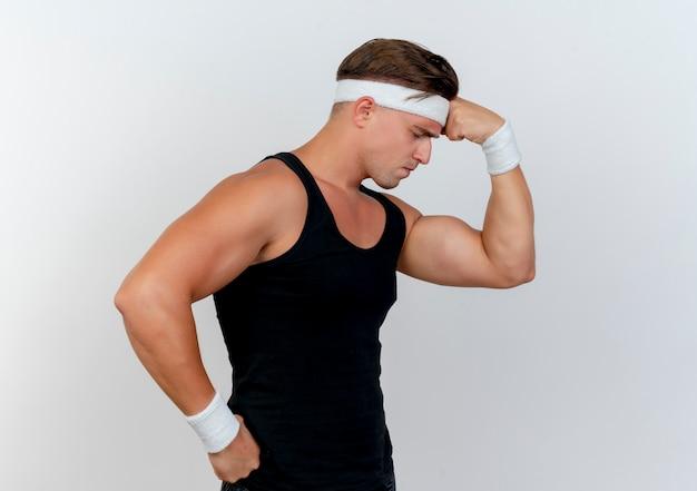 Dolorante giovane uomo sportivo bello che indossa fascia e braccialetti mettendo il pugno sulla fronte e la mano sulla vita che soffrono di mal di testa con gli occhi chiusi isolati su bianco
