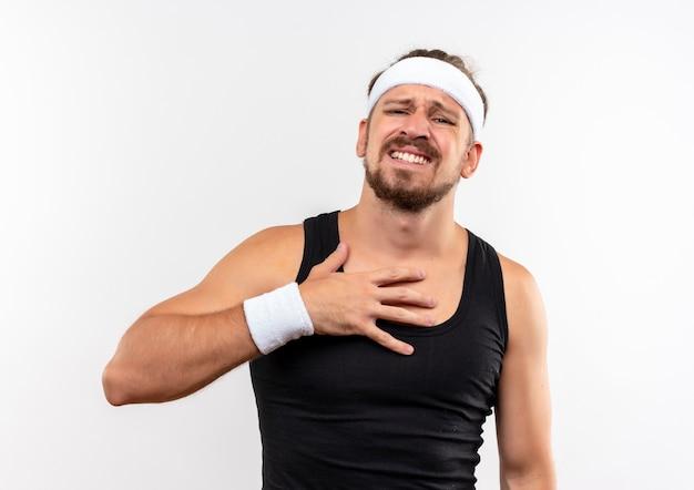 Giovane uomo sportivo bello dolorante che indossa fascia e braccialetti che mettono la mano sul petto guardando isolato sul muro bianco