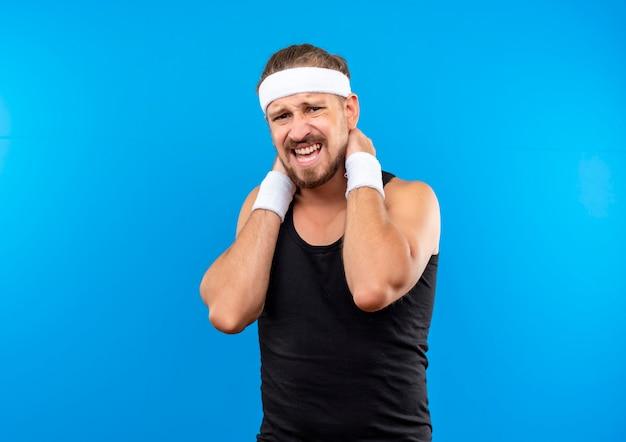 Giovane e bello sportivo dolorante che indossa fascia e braccialetti che si mettono le mani sul collo isolato sulla parete blu con spazio per le copie