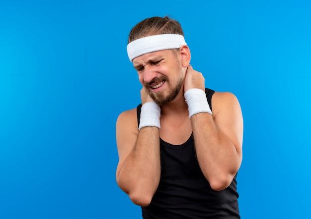 Giovane e bello sportivo dolorante che indossa fascia e braccialetti che mettono le mani sul collo guardando in basso isolato sulla parete blu con spazio di copia