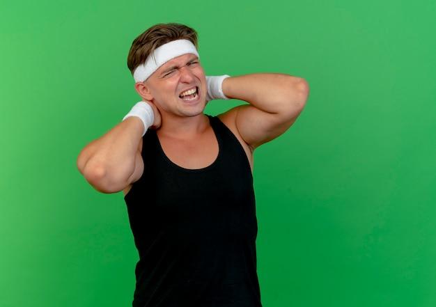 Giovane uomo sportivo bello dolorante che indossa la fascia e braccialetti che mettono le mani dietro il collo che soffrono di dolore isolato su verde con lo spazio della copia