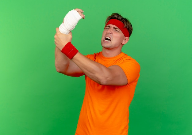 Aching young handsome sporty man wearing headband and wristbands raising and holding his injured wrist wrapped with bandage isolated on green  with copy space
