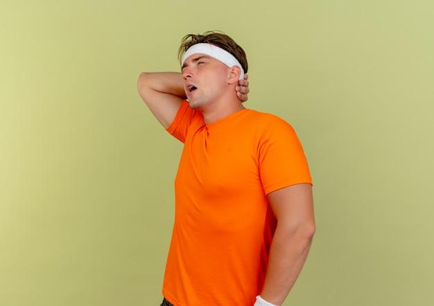 Dolorante giovane uomo sportivo bello che indossa fascia e braccialetti in piedi in vista di profilo mettendo la mano dietro il collo guardando dritto isolato su verde oliva con spazio di copia