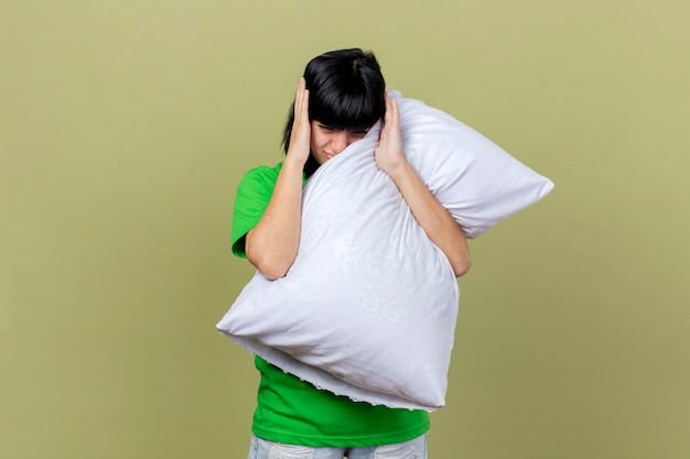 Больная молодая больная кавказская девушка держит подушку и смотрит прямо, держа руки на голове, изолированной на оливково-зеленой стене с копией пространства