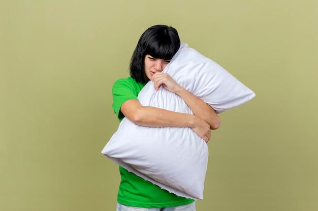 Giovane ragazza caucasica malata dolorante che abbraccia il cuscino che guarda giù isolato sulla parete verde oliva con lo spazio della copia