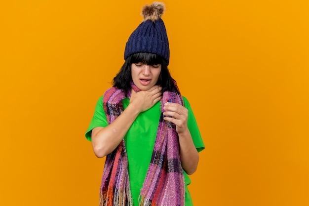 Giovane ragazza caucasica malata dolorante che indossa cappello invernale e sciarpa tenendo le capsule tenendo la mano sulla gola con gli occhi chiusi isolati su sfondo arancione con spazio di copia