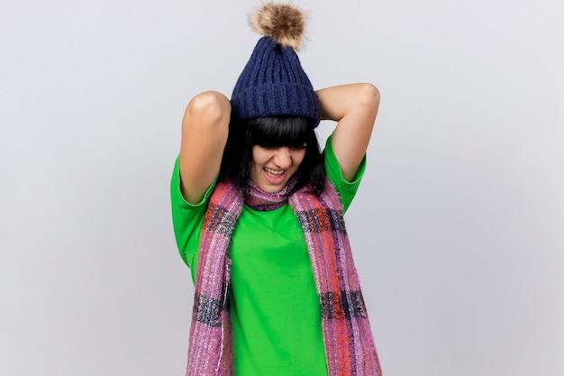 Giovane ragazza caucasica malata dolorante che indossa il cappello e la sciarpa di inverno che tengono le mani dietro la schiena con gli occhi chiusi isolati sulla parete bianca con lo spazio della copia