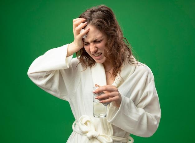 緑で隔離の額に手を置いて水のガラスを保持している白いローブを着て痛む若い病気の女の子