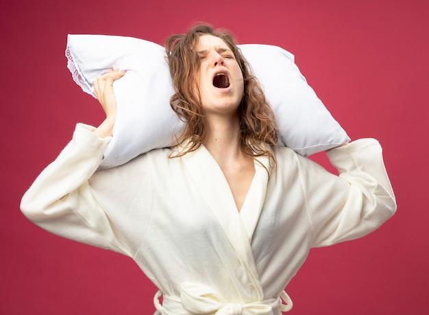 Болит молодая больная девушка в белом халате, держащая подушку за головой, изолированную на розовом