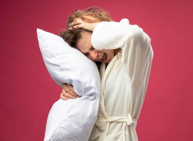 Больная молодая больная девушка в белом халате обняла подушку, схватила голову, изолированную на розовом