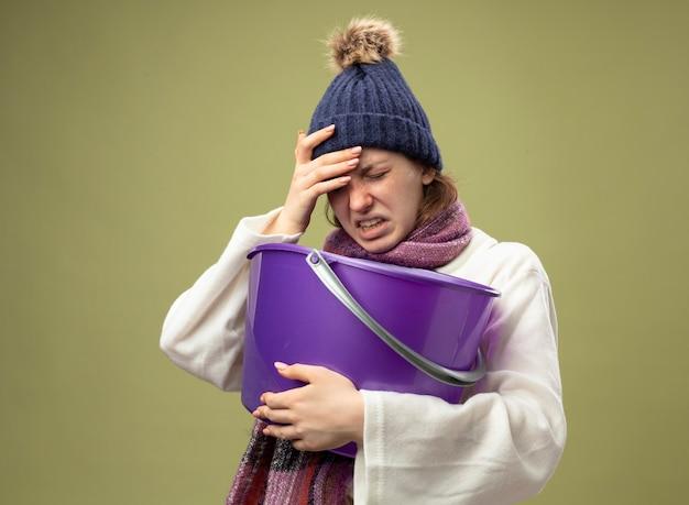 Giovane ragazza malata dolorante che indossa una veste bianca e cappello invernale con la sciarpa che tiene il secchio di plastica che mette la mano sulla fronte isolata su verde oliva