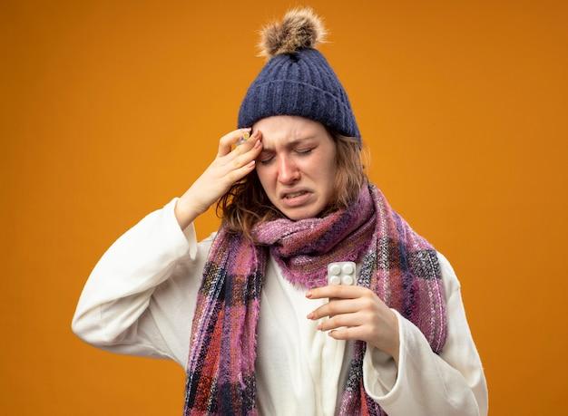 Giovane ragazza malata dolorante che indossa una veste bianca e cappello invernale con la sciarpa che tiene la siringa con le pillole che mettono la mano sulla fronte isolata sulla parete arancione