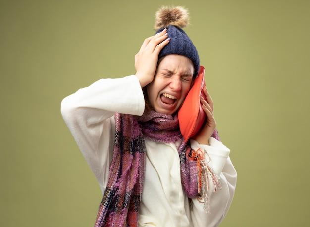 Dolorante giovane ragazza malata che indossa una tunica bianca e cappello invernale con sciarpa che mette la borsa dell'acqua calda sulla guancia ha afferrato la testa isolata su verde oliva