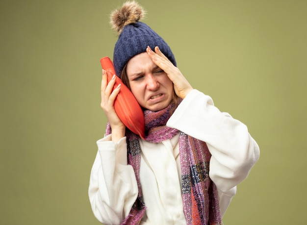 Dolorante giovane ragazza malata che indossa una veste bianca e cappello invernale con sciarpa mettendo la borsa dell'acqua calda sulla guancia mettendo la mano sul tempio isolato su verde oliva