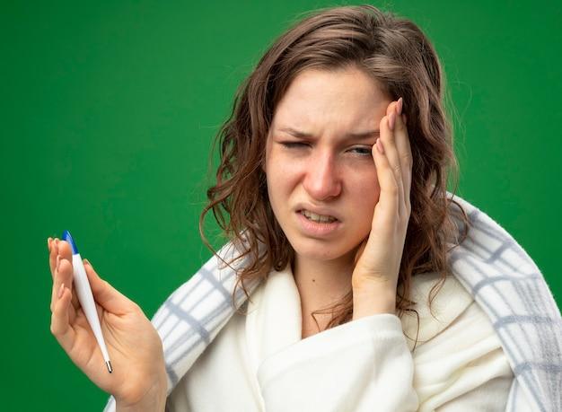 Больная молодая больная девушка в белом халате, завернутая в плед, держит термометр, положив руку на храм, изолированный на зеленом