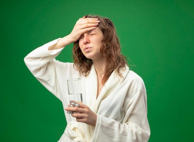 Giovane ragazza malata dolorante con gli occhi chiusi che indossa una veste bianca che tiene il bicchiere d'acqua e mette la mano sulla fronte isolata sul verde