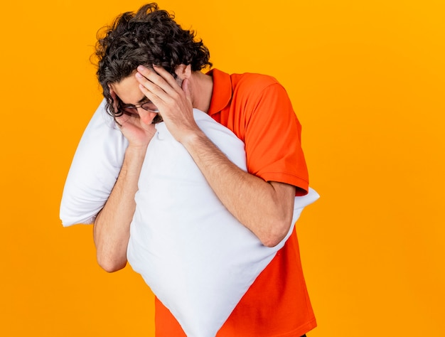 Dolorante giovane uomo malato con gli occhiali che abbraccia cuscino tenendo la testa con gli occhi chiusi isolati sulla parete arancione