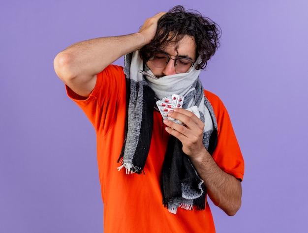 Dolorante giovane uomo malato con gli occhiali e sciarpa mettendo la mano sulla testa che tiene pillole mediche con gli occhi chiusi isolati sulla parete viola