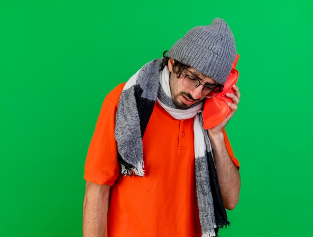 眼鏡の冬の帽子とスカーフを身に着けている痛む若い病気の人がコピースペースで緑の壁に隔離された目を閉じて湯たんぽを頭に置く