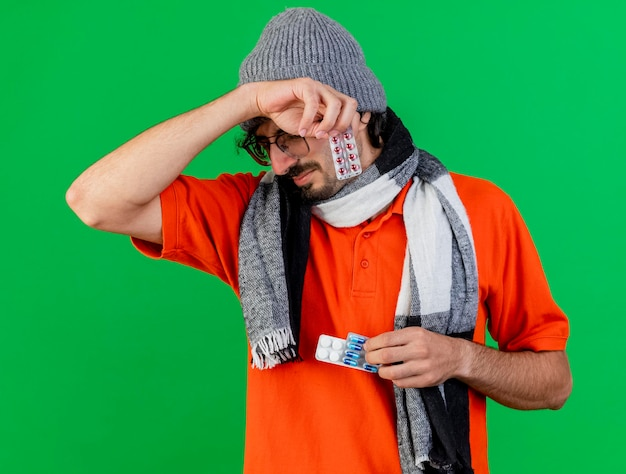 Aching young ill man wearing glasses winter hat and scarf holding medical pills touching head isolated on green wall