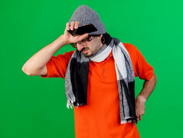 Giovane malato dolorante che indossa occhiali inverno cappello e sciarpa tenendo il telefono cellulare e il tovagliolo tenendo la mano sulla testa isolata sulla parete verde
