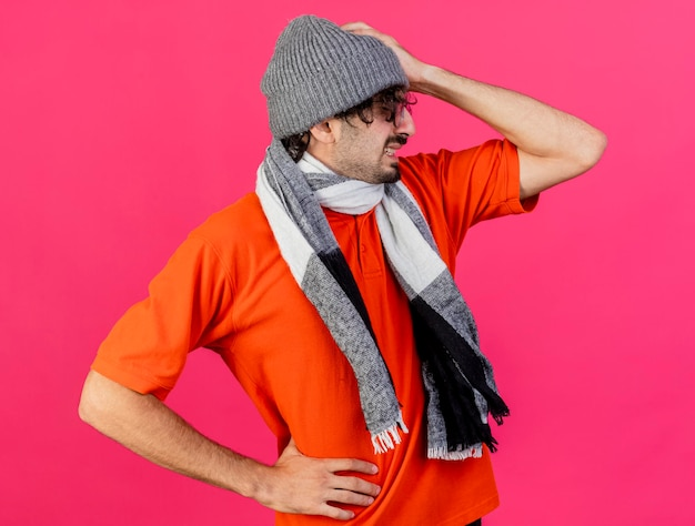 Aching young ill man wearing glasses winter hat and scarf keeping hands on waist and on head looking at side with closed eyes isolated on pink wall
