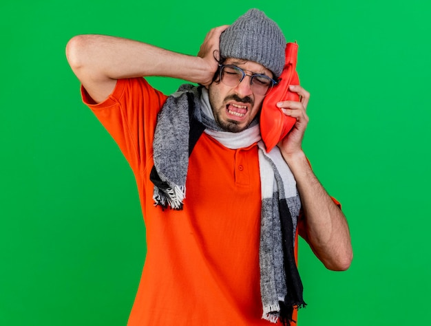 Aching young ill man wearing glasses winter hat and scarf putting hot water bag on head keeping hand on head with closed eyes isolated on green wall