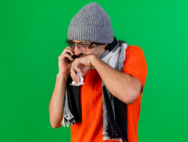 Giovane uomo malato dolorante che indossa occhiali inverno cappello e sciarpa parlando al telefono tenendo il tovagliolo tenendo la mano sulla bocca guardando in basso isolato sulla parete verde con spazio di copia