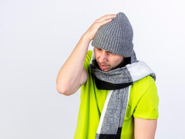 Il giovane malato dolorante che indossa il cappello e la sciarpa di inverno mette la mano sulla testa isolata sulla parete bianca