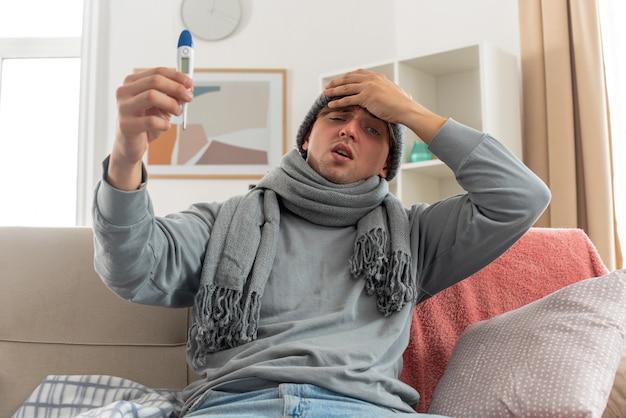 목에 스카프를 두른 아픈 젊은 남자가 겨울 모자를 쓰고 이마에 손을 대고 거실 소파에 앉아 온도계를 들고 있다