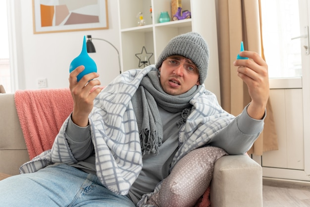 Dolorante giovane uomo malato con sciarpa intorno al collo indossando cappello invernale avvolto in plaid tenendo clisteri seduto sul divano in soggiorno