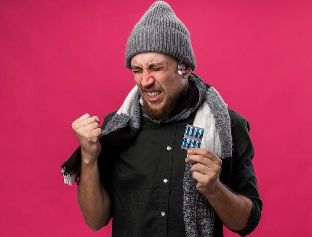 冬の帽子をかぶって首にスカーフを身に着けている痛む若い病気のスラブ人は拳を保ち、さまざまな薬のパックを保持します