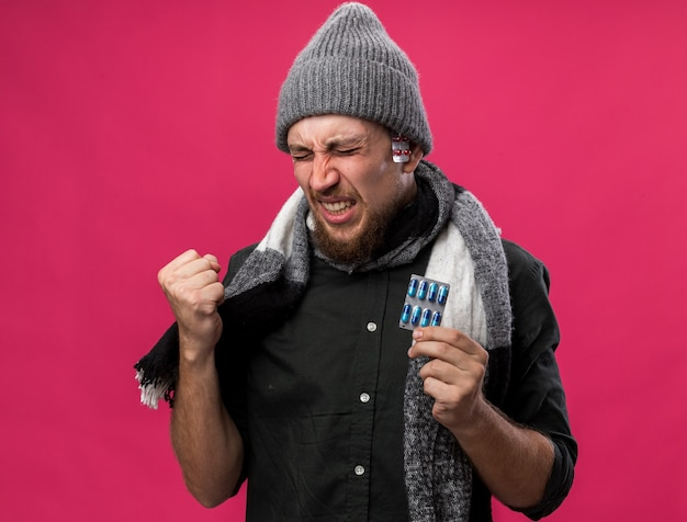 Aching young ill slavic man with scarf around neck wearing winter hat keeps fist and holds different medicine packs
