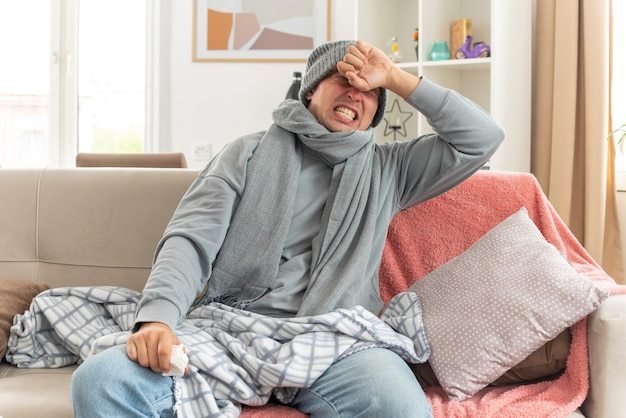 Dolorante giovane malato uomo slavo con sciarpa intorno al collo indossando cappello invernale mettendo la mano sulla fronte e tenendo il tessuto seduto sul divano in soggiorno