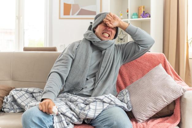 Болит молодой больной славянский мужчина с шарфом на шее в зимней шапке, положив руку на лоб и держа салфетку, сидя на диване в гостиной