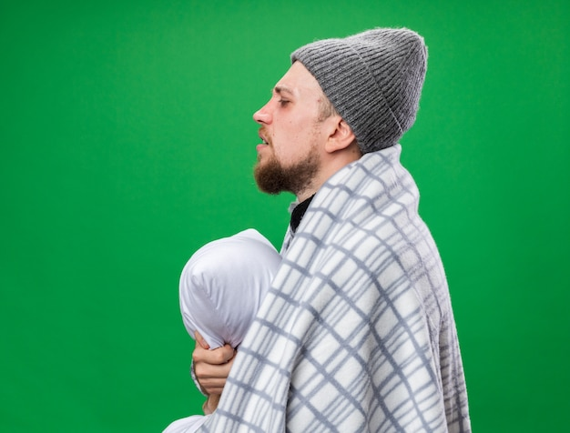 Aching young ill slavic man with scarf around neck wrapped in plaid wearing winter hat stands sideways holding pillow isolated on green wall with copy space