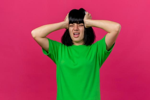 Giovane donna malata dolorante che tiene la testa con gli occhi chiusi isolato sulla parete rosa con lo spazio della copia
