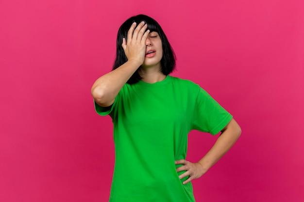 복사 공간 핑크 벽에 고립 된 닫힌 된 눈으로 허리에 손을 유지하는 얼굴에 손을 넣어 아프고 젊은 아픈 여자