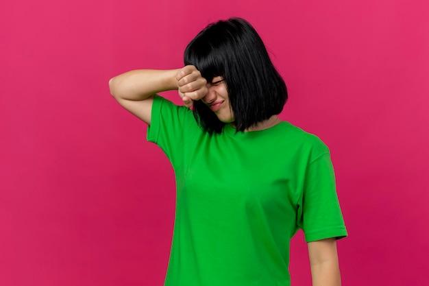 コピースペースとピンクの壁に隔離された目を閉じて頭痛に苦しんで頭に手を置く痛む若い病気の女性