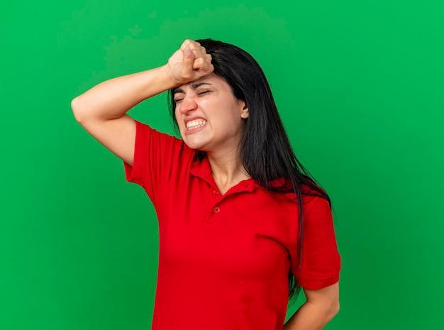 아픈 젊은 아픈 여자 복사 공간이 녹색 벽에 고립 된 두통을 앓고 닫힌 눈으로 머리에 손을 넣어
