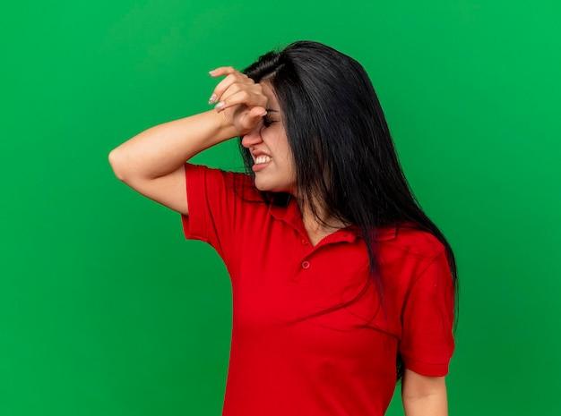 녹색 벽에 고립 된 두통을 앓고 닫힌 눈으로 머리에 손을 넣어 아프고 젊은 아픈 여자